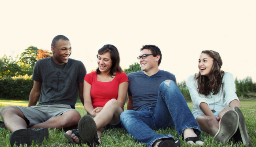 Young people sitting in garden smiling together
