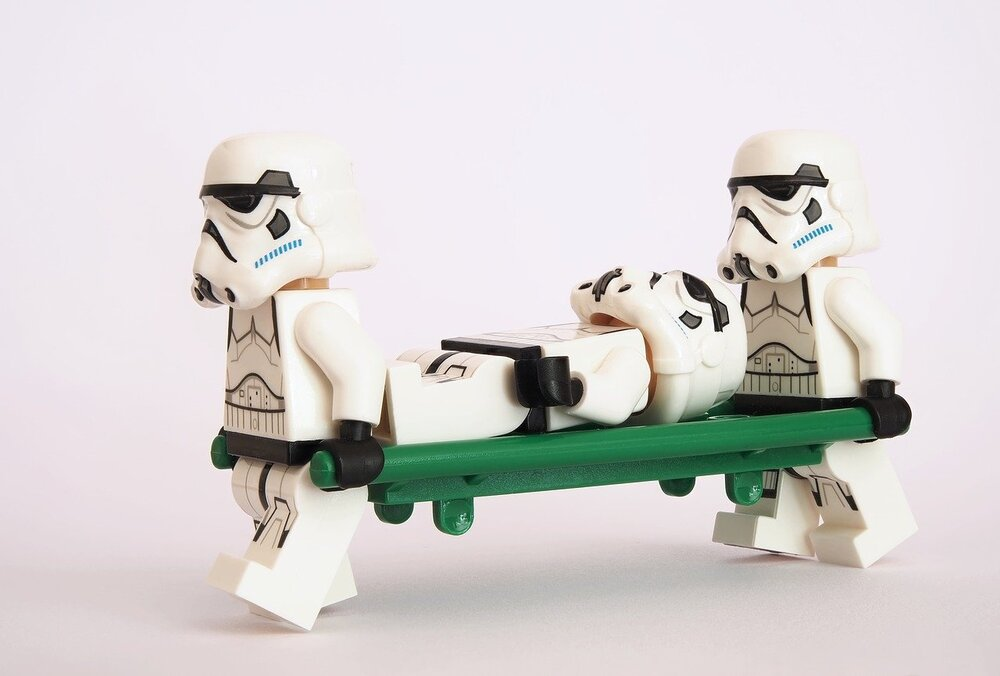Stromtroopers carrying injured stormtrooper in stretcher